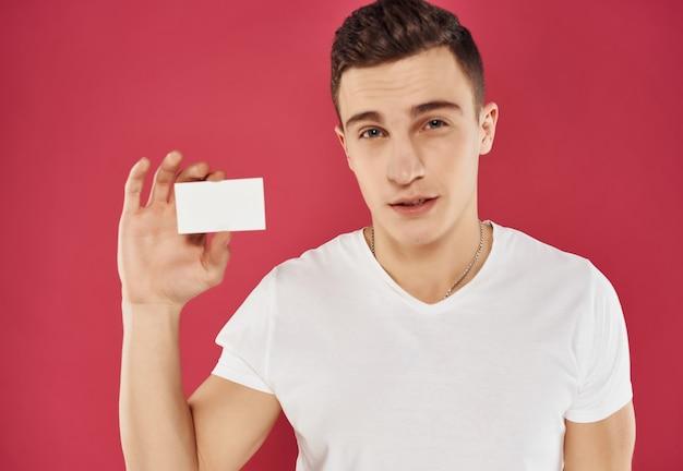 Homem bonito com um cartão de visita nas mãos, gerente de publicidade profissional