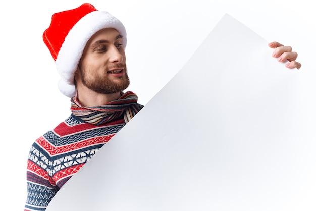 Homem bonito com um chapéu de natal e um pôster de maquete branco estúdio copyspace