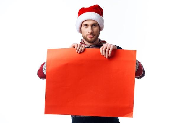 Homem bonito com um chapéu de natal e uma maquete vermelha com o estúdio do copyspace