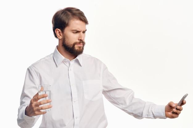 Homem bonito com um copo de água luz de camisa branca estilo de vida saudável