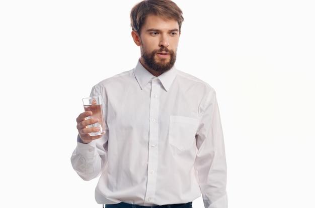 Homem bonito com um copo de água parede de luz de camisa branca estilo de vida saudável.
