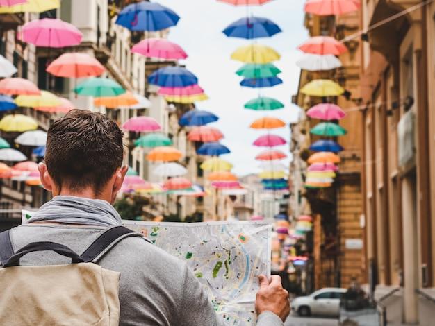 Homem bonito com um mapa turístico em um dia nublado