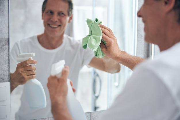 Homem bonito com um sorriso no rosto enquanto faz a limpeza da casa
