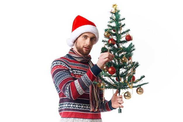 Homem bonito com uma árvore nas mãos enfeites de férias divertidas em estúdio posando