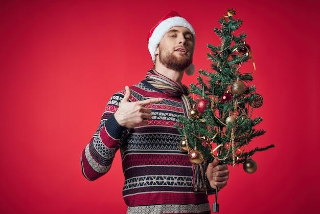Homem bonito com uma árvore nas mãos, enfeites de férias divertidas fundo vermelho