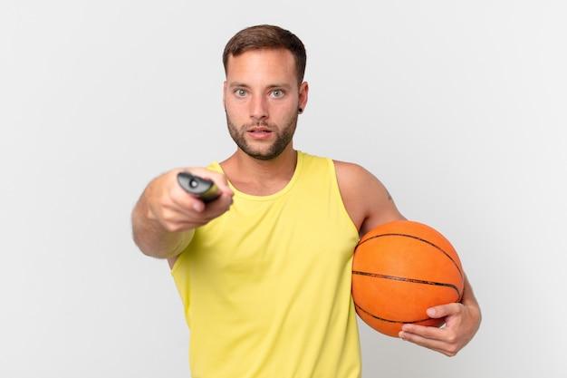 Homem bonito com uma bola de basquete e escolhendo um canal com um controlador