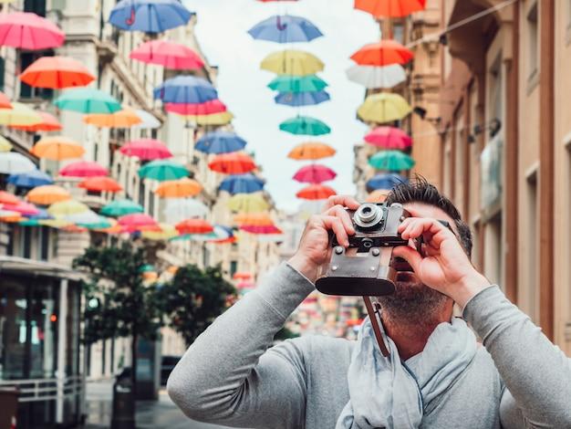 Homem bonito com uma câmera vintage em um dia chuvoso.