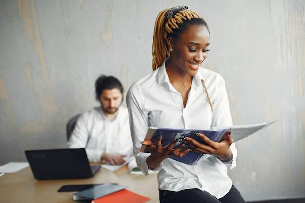 Homem bonito com uma camisa branca. mulher africana com parceiro. cara com um laptop.