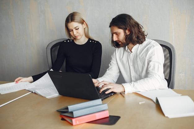 Homem bonito com uma camisa branca. parceiros juntos. cara com um laptop.