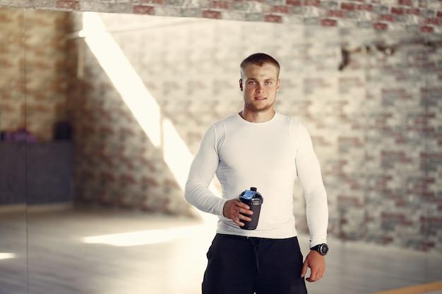 Homem bonito com uma garrafa de água em uma academia