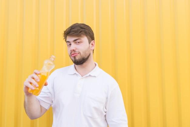 Homem bonito com uma garrafa de bebida está de pé em uma parede amarela