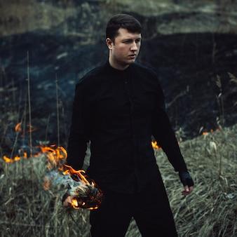 Homem bonito com uma tocha nas mãos ateará fogo à grama no campo