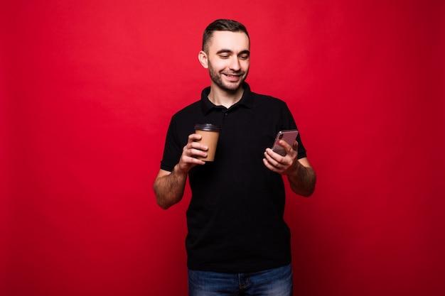 Homem bonito com uma xícara de café para ir ler notícias no telefone isolado sobre fundo vermelho