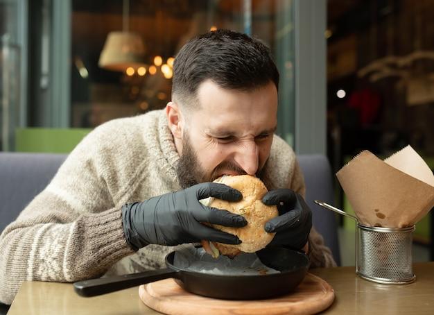 Homem bonito comendo hambúrguer saboroso em um café