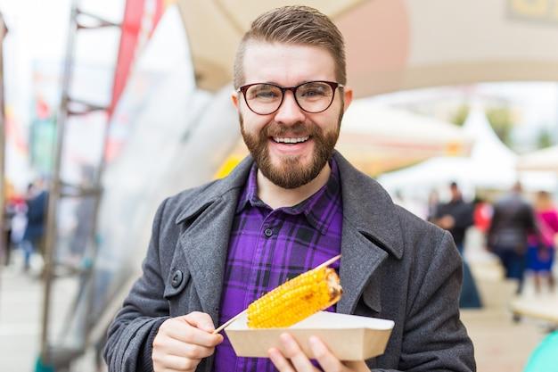 Homem bonito comendo milho torrado na rua.