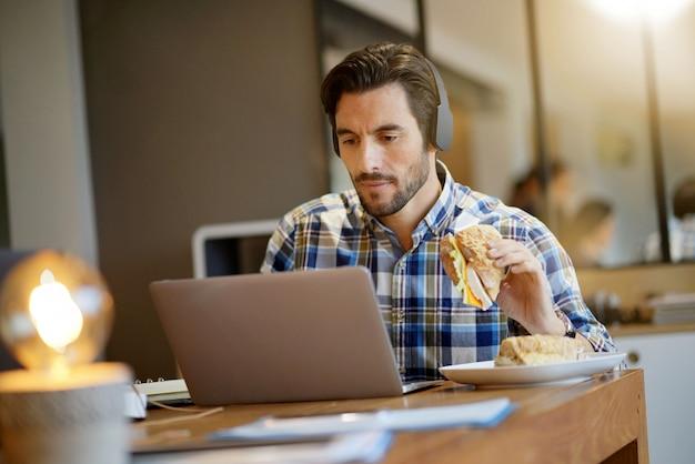 Homem bonito comer o almoço no trabalho