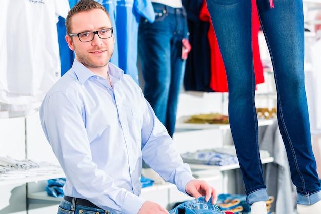 Homem bonito comprando jeans em uma loja ou loja