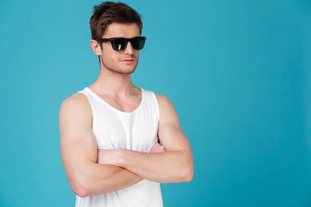 Homem bonito confiante em óculos de sol em pé com os braços cruzados