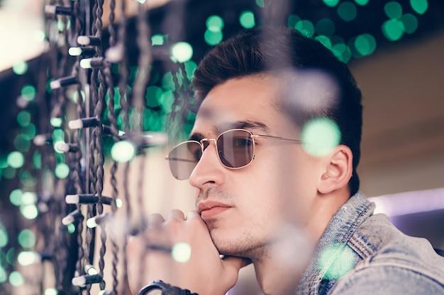 Homem bonito confiante em óculos de sol