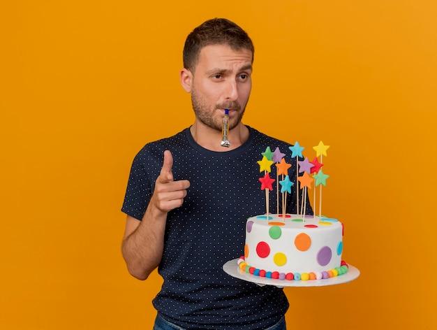 Homem bonito confiante segurando um bolo de aniversário, soprando um apito e apontando para a frente, isolado na parede laranja