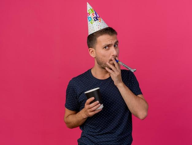 Homem bonito confiante usando boné de aniversário segurando um copo de papel, soprando um apito isolado na parede rosa com espaço de cópia