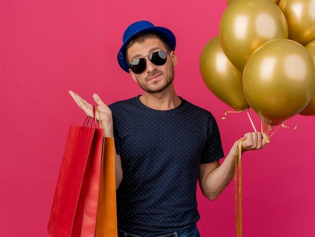 Homem bonito confiante usando óculos de sol e chapéu de festa azul segurando balões de hélio e sacolas de papel isoladas na parede rosa