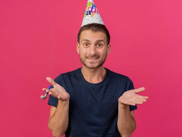 Homem bonito confuso com boné de aniversário e mãos abertas apito isolado na parede rosa