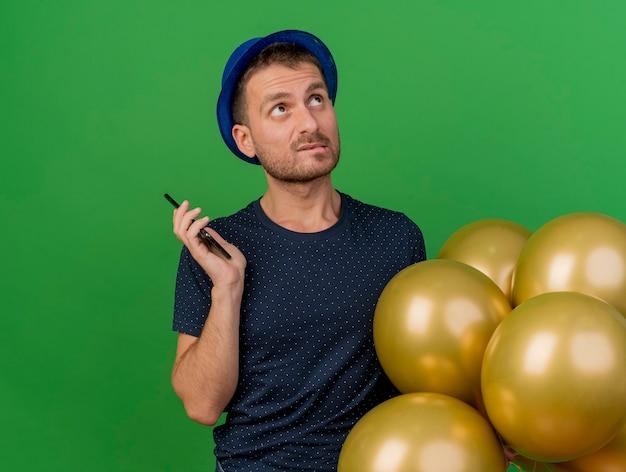 Homem bonito confuso com chapéu de festa azul segurando balões de hélio e telefone olhando para cima, isolado na parede verde
