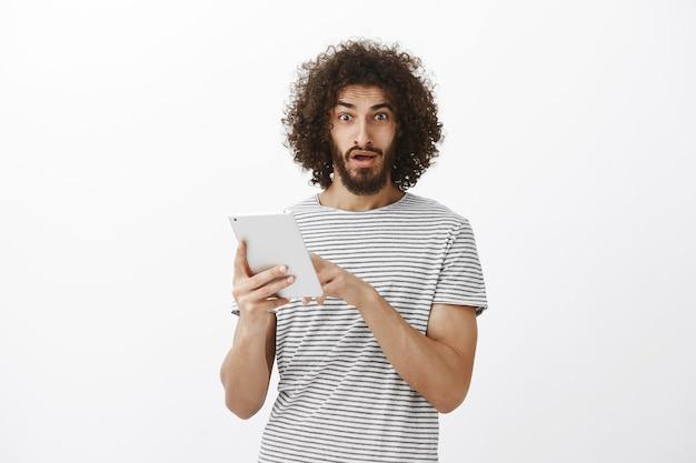 Homem bonito confuso e frustrado com barba e corte de cabelo afro, apontando para a tela do tablet digital e caindo de queixo, vendo notícias estranhas incríveis