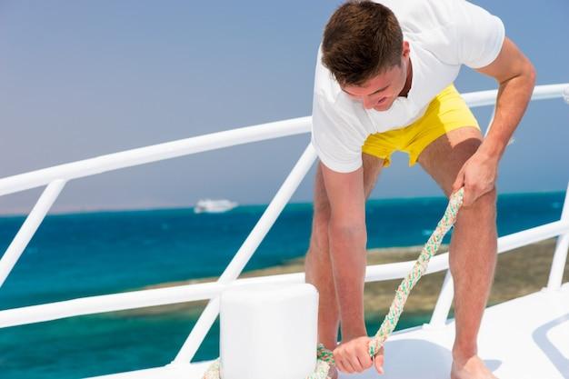 Homem bonito conserta diligentemente a corda de um iate em um dia ensolarado de verão, lindo mar no fundo