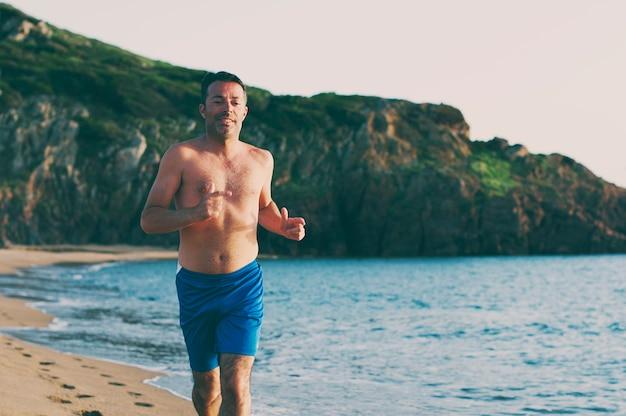 Homem bonito correndo na praia ao pôr do sol