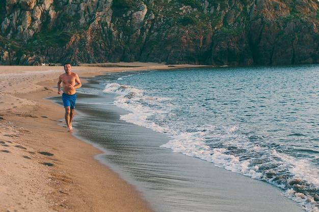 Homem bonito correndo na praia do pôr do sol