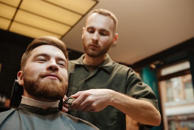 Homem bonito, cortando cabelo de barba de cabeleireiro enquanto está sentado na cadeira de barbearia.