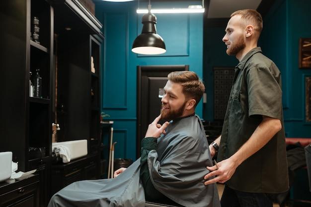 Homem bonito, cortando cabelo de cabeleireiro enquanto está sentado na cadeira.