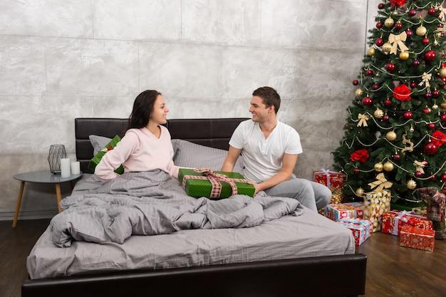 Homem bonito dando um presente para sua esposa feliz, enquanto ela esconde um presente nas costas no quarto em estilo loft com árvore de natal com muitos presentes