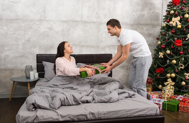 Homem bonito dando um presente para sua namorada feliz, enquanto ela está sentada em uma cama e de pijama no quarto em estilo loft com árvore de natal com muitos presentes