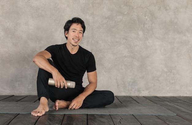 Homem bonito, dando um tempo de exercício. ele está sentado em uma esteira, segurando uma garrafa de água.