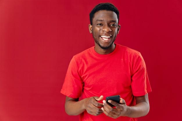 Homem bonito de aparência africana em um espaço de cópia de fundo vermelho