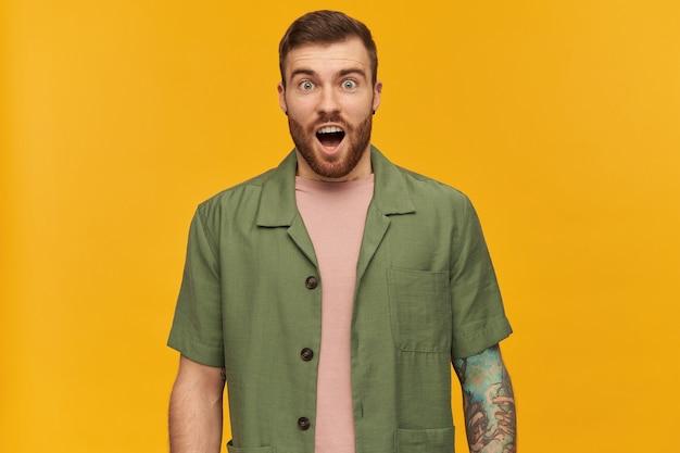 Homem bonito, de aparência chocada, com cabelo e barba morena. jaqueta verde de mangas curtas. possui tatuagem e piercing. com boca aberta, isolada sobre parede amarela