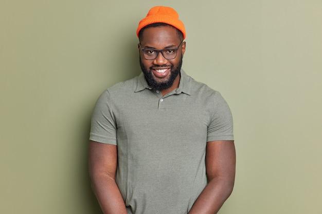 Homem bonito de barba negra sorri feliz e parece autoconfiante para a câmera, aproveita um bom dia e conversa agradável usa camiseta básica, chapéu laranja e poses de óculos contra a parede do estúdio verde escuro