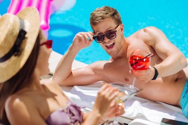 Homem bonito de cabelo escuro usando óculos escuros, rindo alto enquanto brincava com a namorada