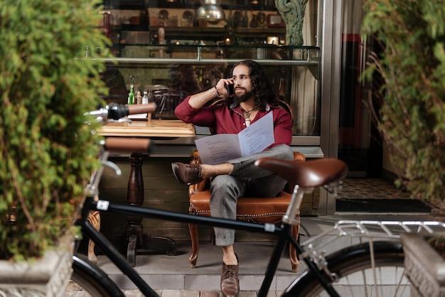 Homem bonito de cabelos compridos fazendo uma ligação enquanto segura o cardápio no restaurante