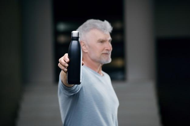 Homem bonito de cabelos grisalhos, camisa branca com garrafa de água. conceito de esporte e saúde