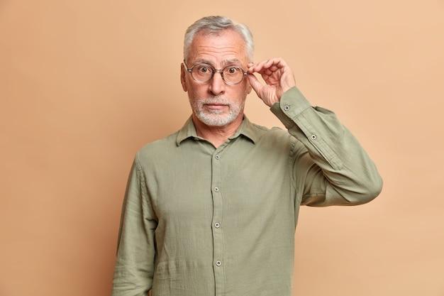Homem bonito de cabelos grisalhos surpreso segurando a borda dos óculos ouve notícias incríveis usando poses formais de camisa contra a parede marrom