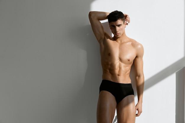 Homem bonito de calcinha preta posando em um modelo de fundo claro