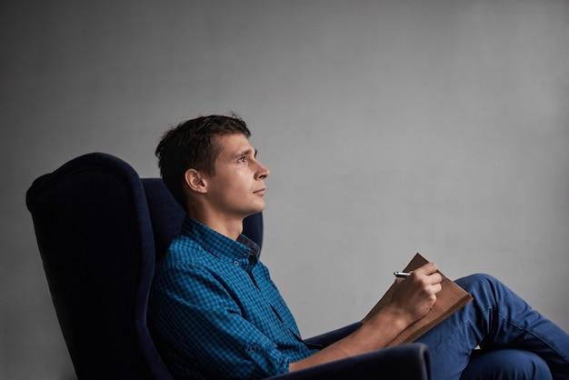 Homem bonito de camisa azul e calça jeans, sentado na cadeira escura e escrevendo ideias no bloco de notas