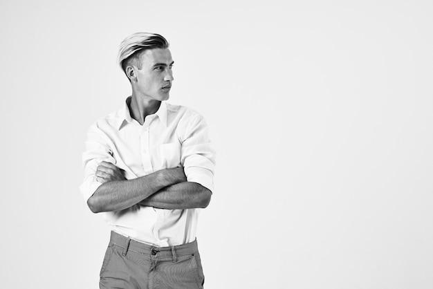 Homem bonito de camisa branca mantém sua mão atrás de sua cabeça elegante estilo de vida. foto de alta qualidade