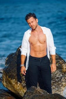 Homem bonito de camisa branca na praia