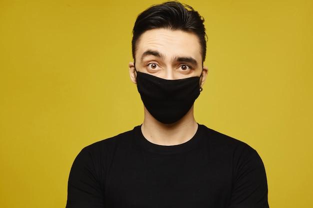 Homem bonito de camiseta preta e preta máscara protetora isolada em fundo amarelo. doença sazonal e conceito de gripe sazonal. conceito de estilo de vida em saúde