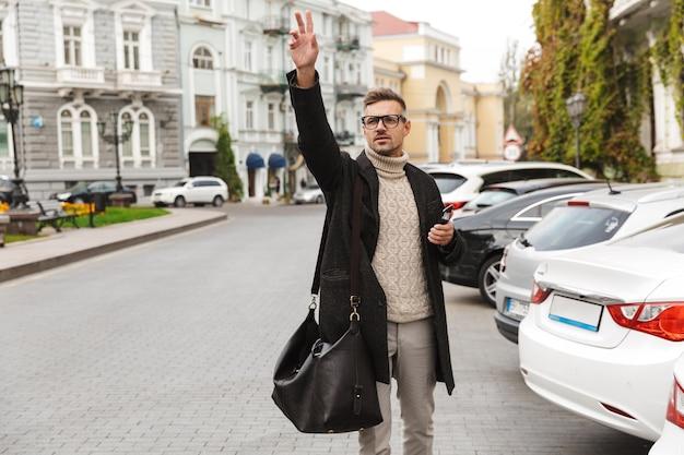 Homem bonito de casaco caminhando ao ar livre, pegando um táxi